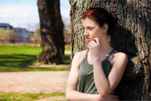 Teenage girl leaning to tree in park